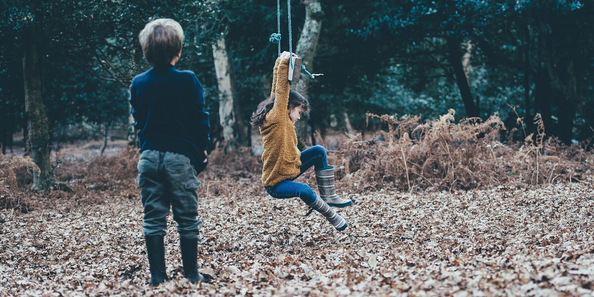 two children playing on a swing