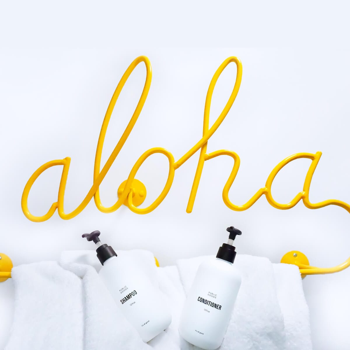 aloha sign, public goods shampoo and conditioner bottles, towels