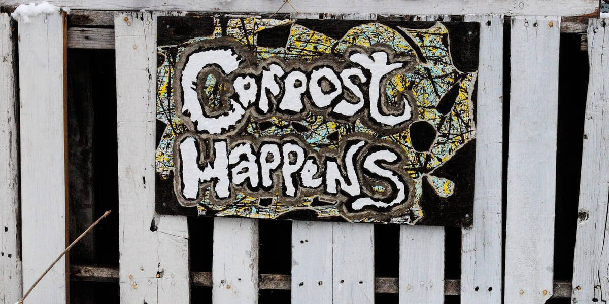painted compost sign on white picket fence