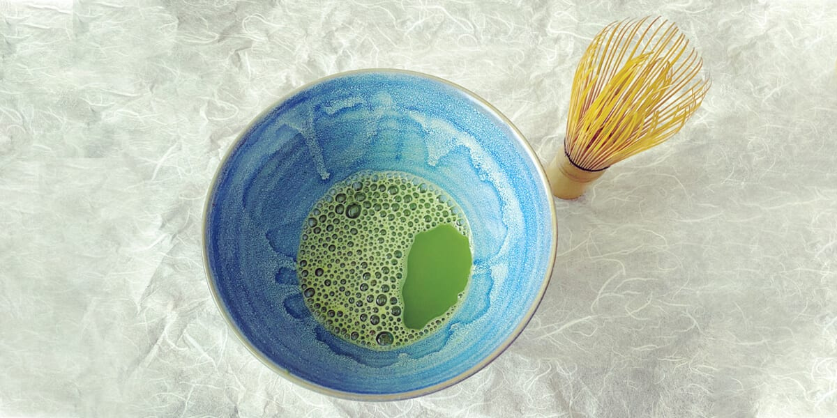 stirred matcha powder in tea bowl, bamboo whisk