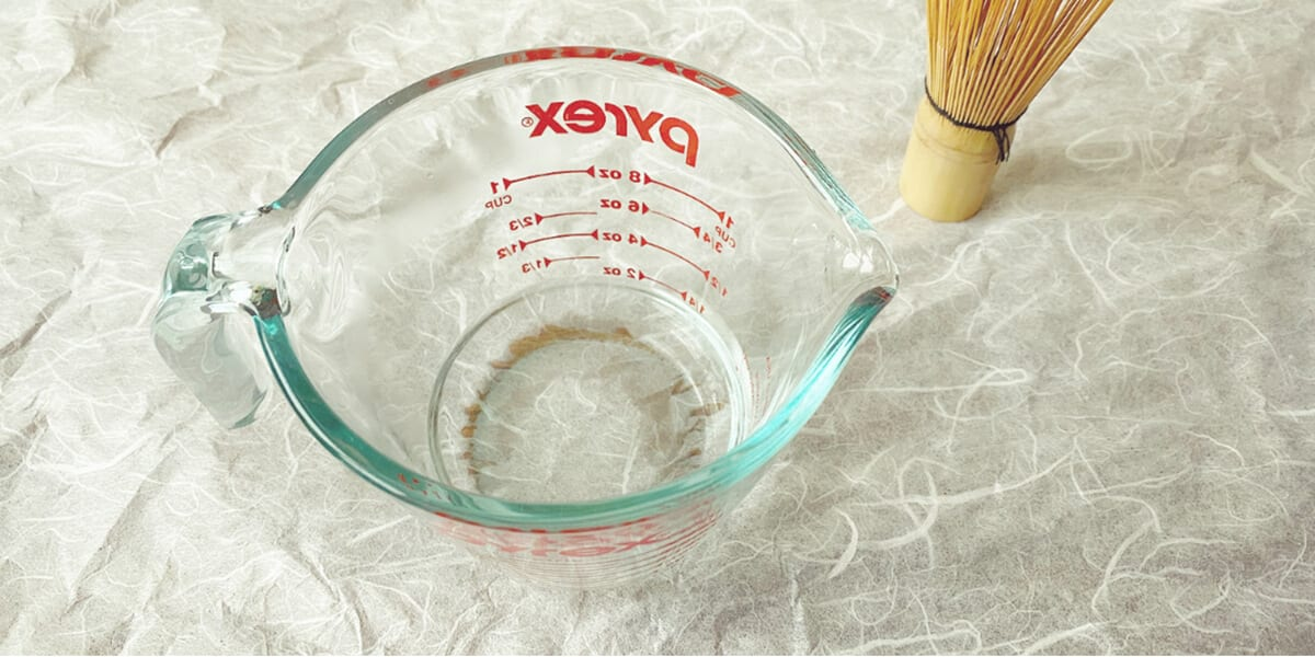 pyrex filled with water next to bamboo whisk