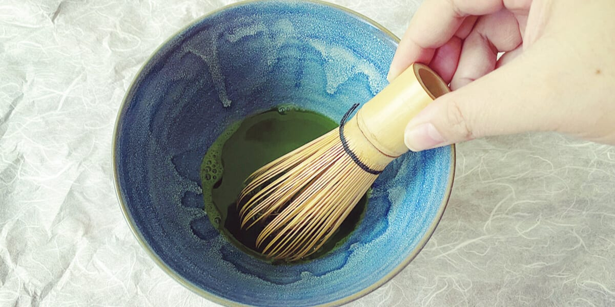 hand stirring matcha powder with bamboo whisk