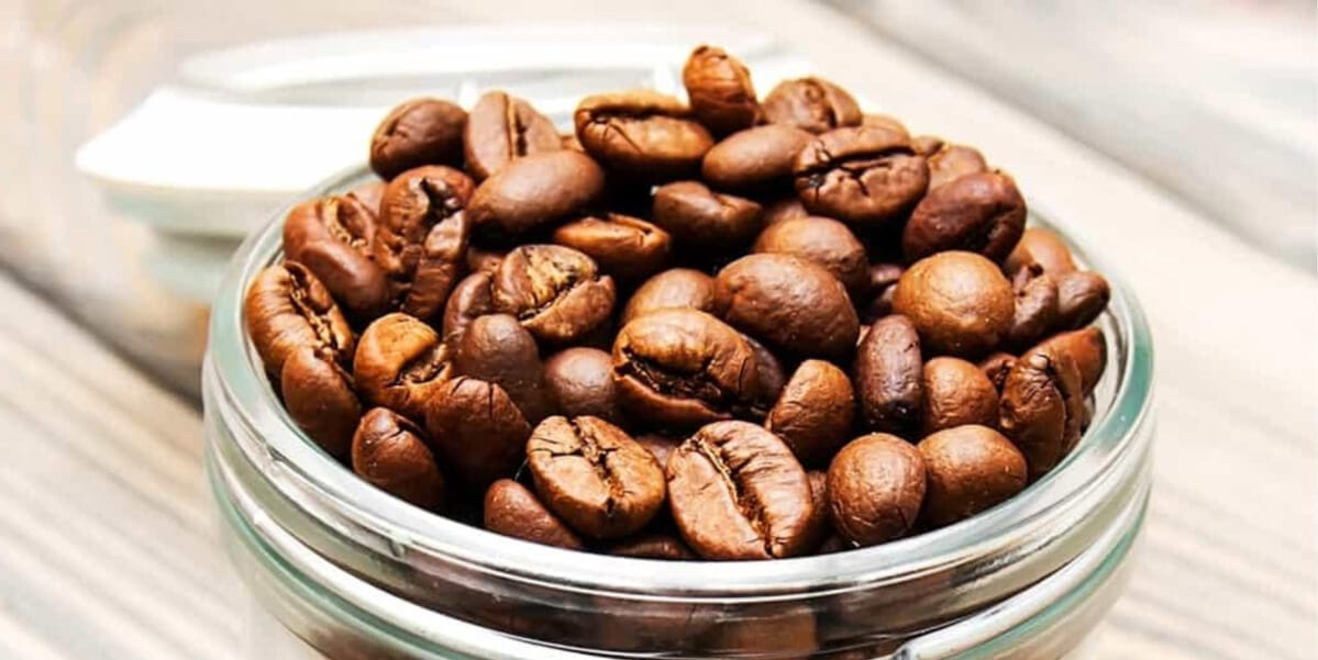 glass jar filled with whole coffee beans