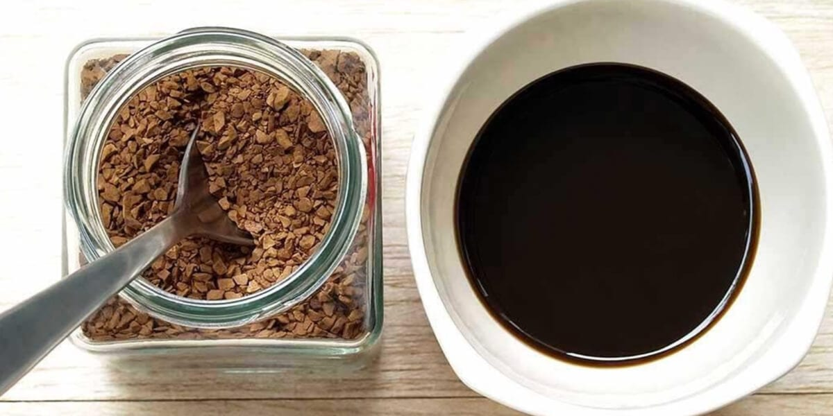 glass jar filled with ground coffee, spoon, cup of fresh coffee