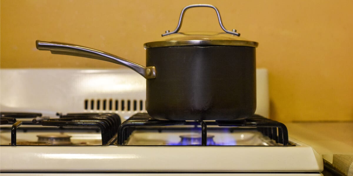 cooking pot with lid on stovetop, ignited stovetop flame