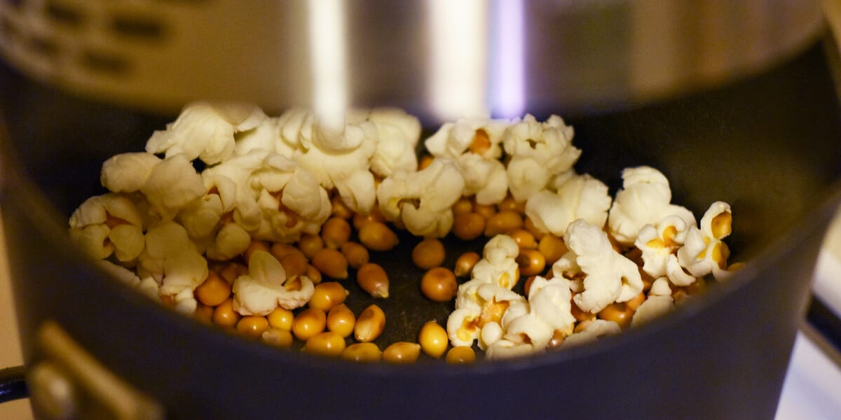 popcorn and popcorn kernels popping in cooking pot on stovetop