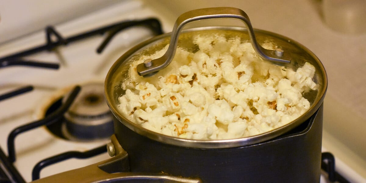popcorn in a cooking pot with lid on a stovetop