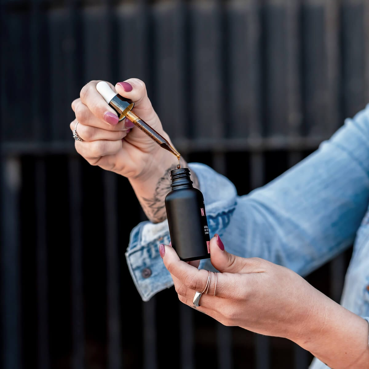woman wearing jean jacket filling a dropper with CBD oil, black CBD oil bottle