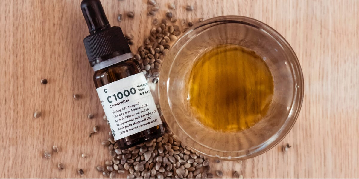 cbd bottle with dropped, hemp seeds, cbd oil in glass cup