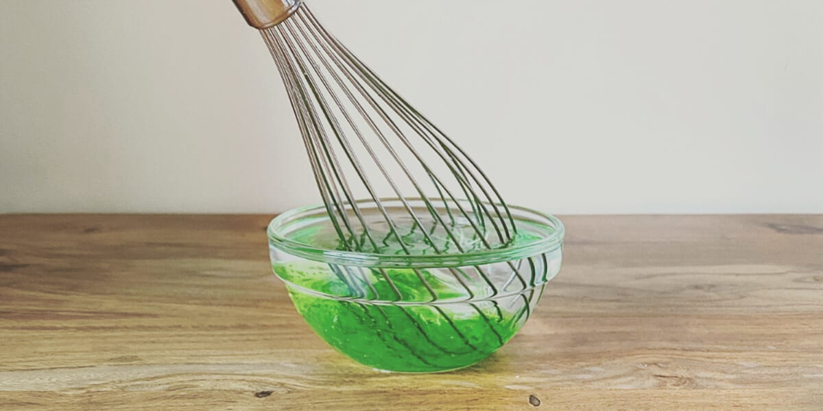 whisk mixing together isopropyl alcohol, essential oil and aloe vera mixture