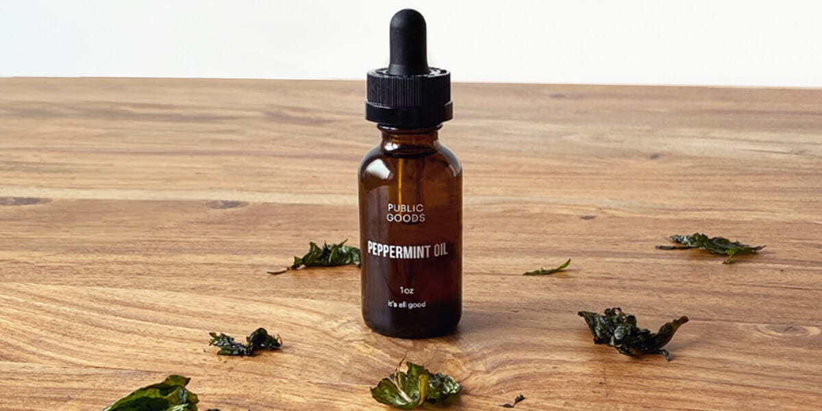 bottle of peppermint oil and wet peppermint leaves on wooden table