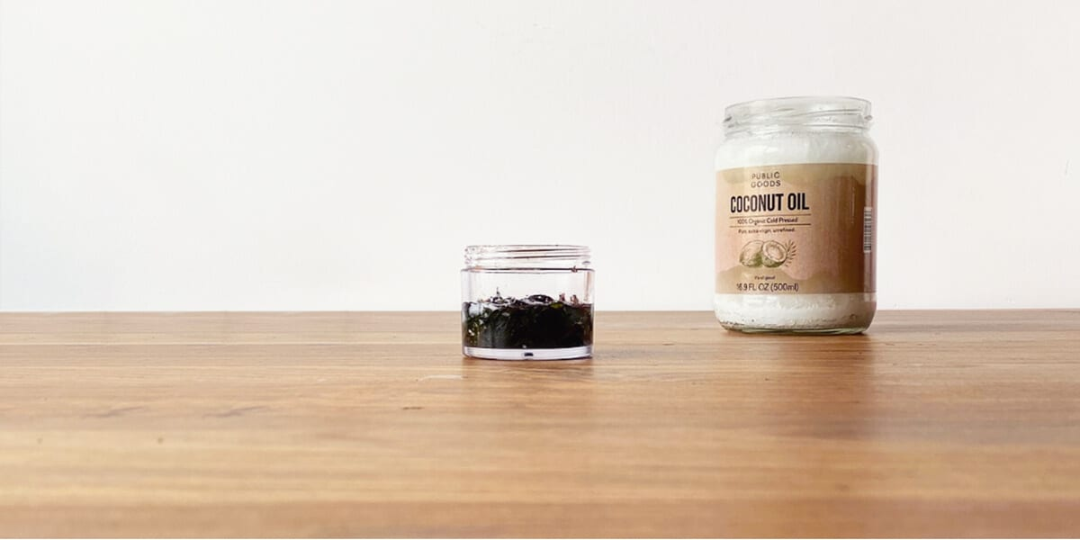 open container with peppermint leaves and carrier oil, jar of coconut oil