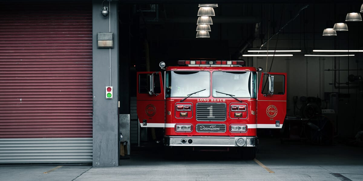 red fire truck with doors opened parked in fire department garage