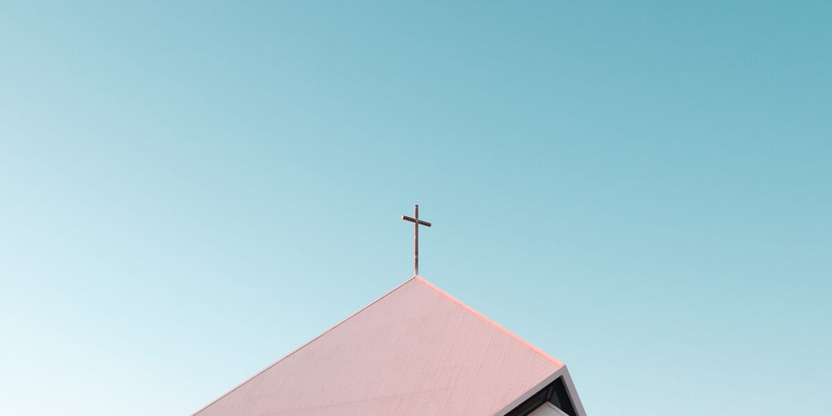 cross on top of church, blue sky