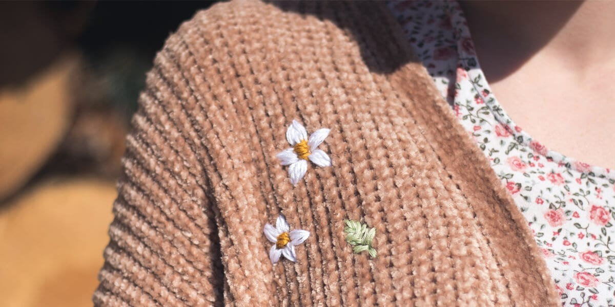 beige cardigan sweater with stitched flowers and a leaf, shoulder, floral shirt