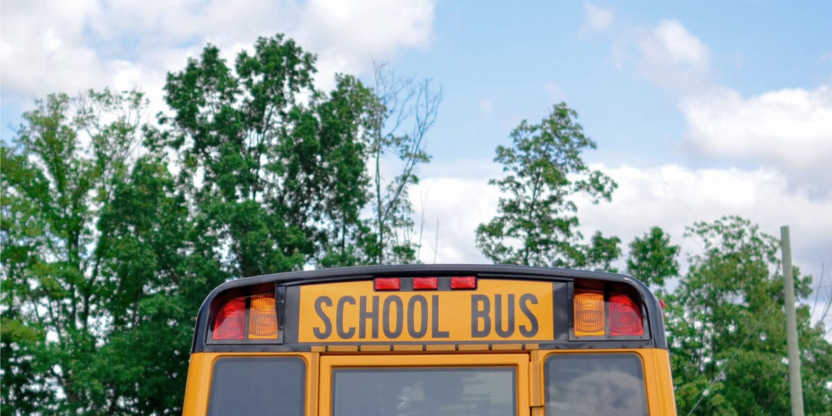 back of a yellow school bus, green trees, blue sky with clouds