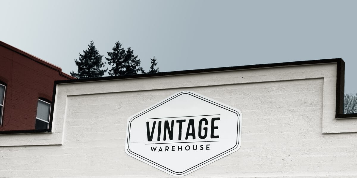 vintage warehouse thrift store, building with brick exterior painted white
