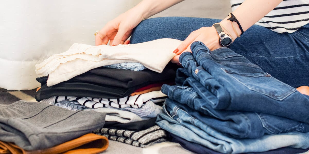 woman folding clean clothes, stacked laundry, blue jeans, striped shirts