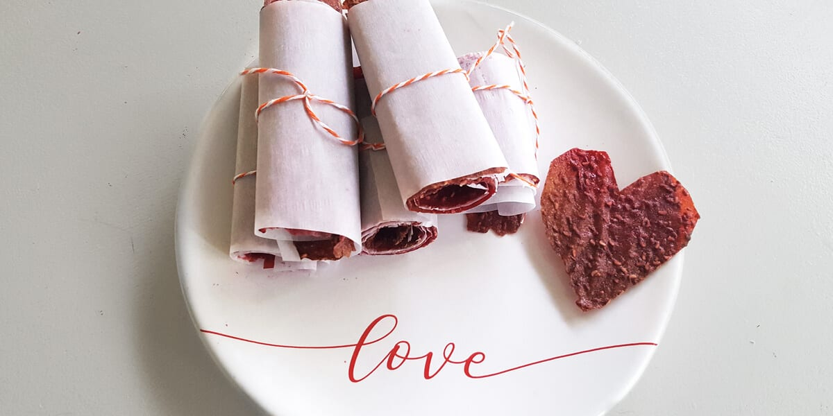 five pieces of rolled up raspberry fruit leather on plate, heart shaped fruit leather