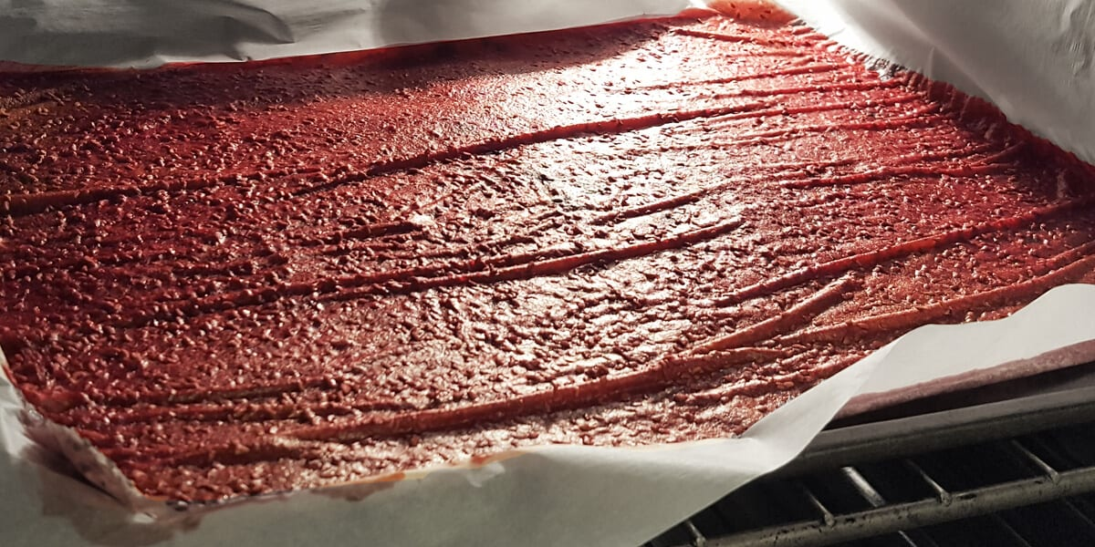 raspberry fruit leather on baking sheet in the oven