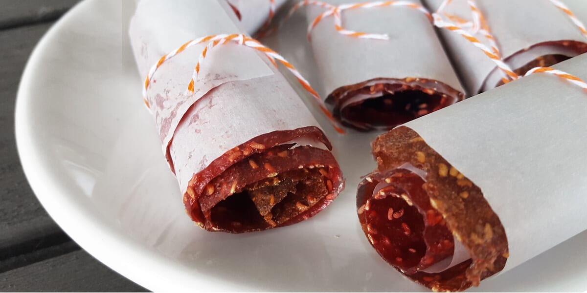 raspberry fruit leather wrapped up in baking sheet on plate