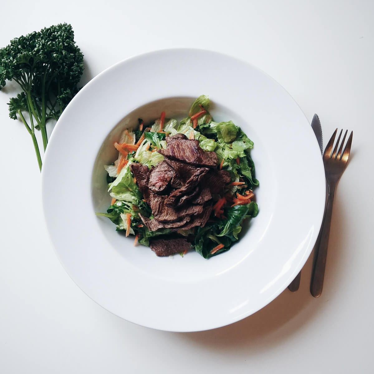 bowl with salad and sliced cooked beef, fork and knife, herbs
