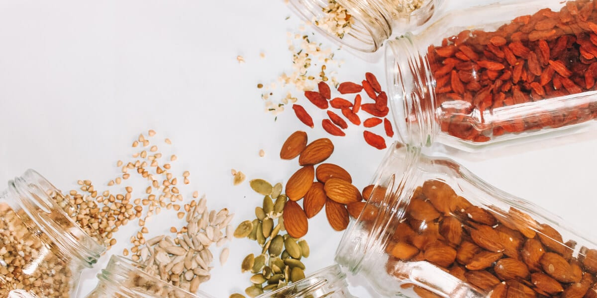 glass jars with almonds, seeds, berries, pistachios