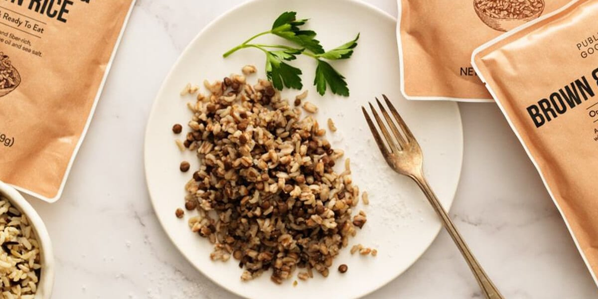plate of whole grains surrounded by public goods brown rice bags