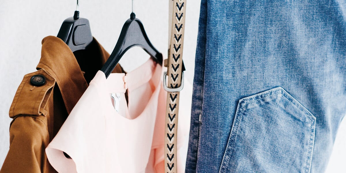 clothing on hangers, blue jeans, belt, pink shirt, brown jacket