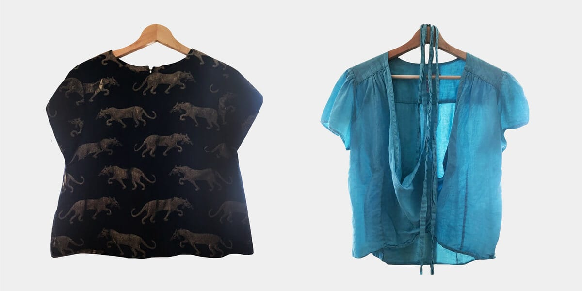 clothing, black top with cheetahs on wooden hanger, light blue top on wooden hanger