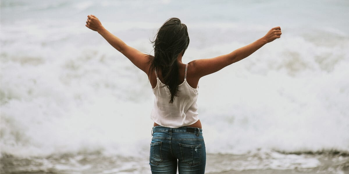 woman standing with arms out in front of the ocean