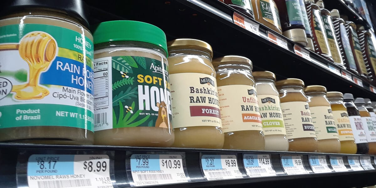 jars of raw honey on grocery store shelf