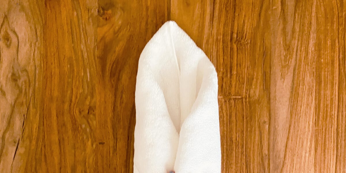 white towel rolled up on wooden table
