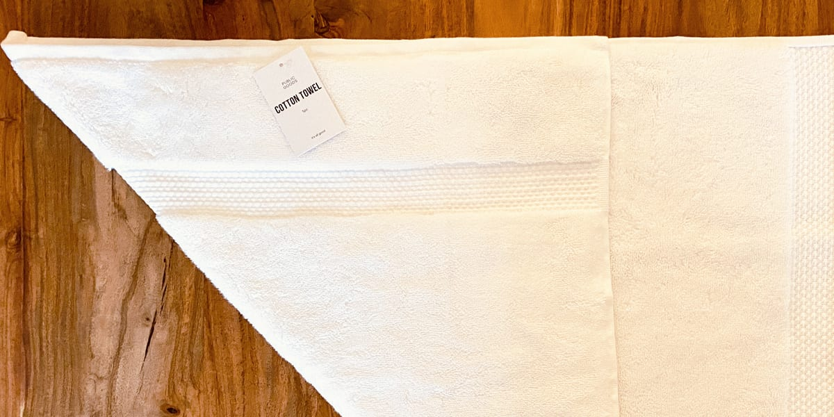 white cotton towel folded over itself on wooden table