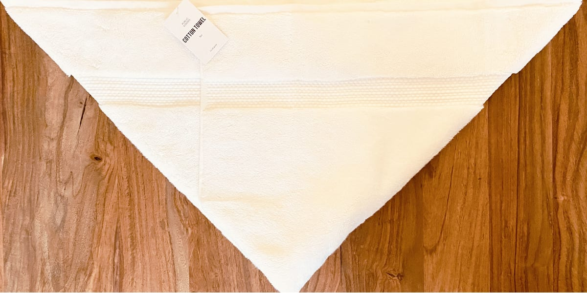 white towel folded in triange shape on wooden table