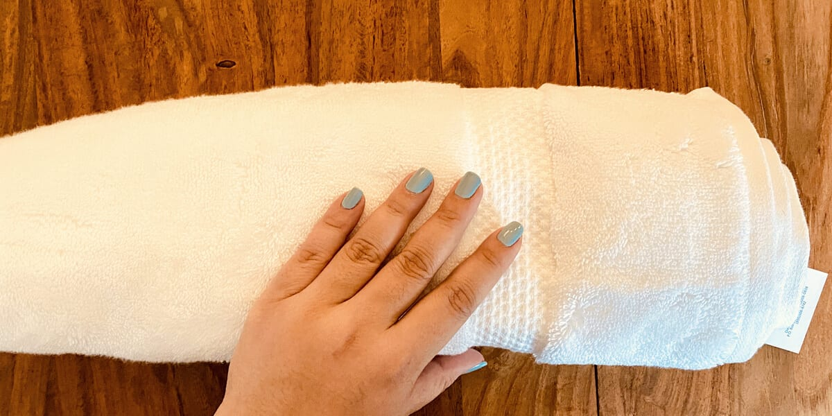 hand rolling up towel on wooden table