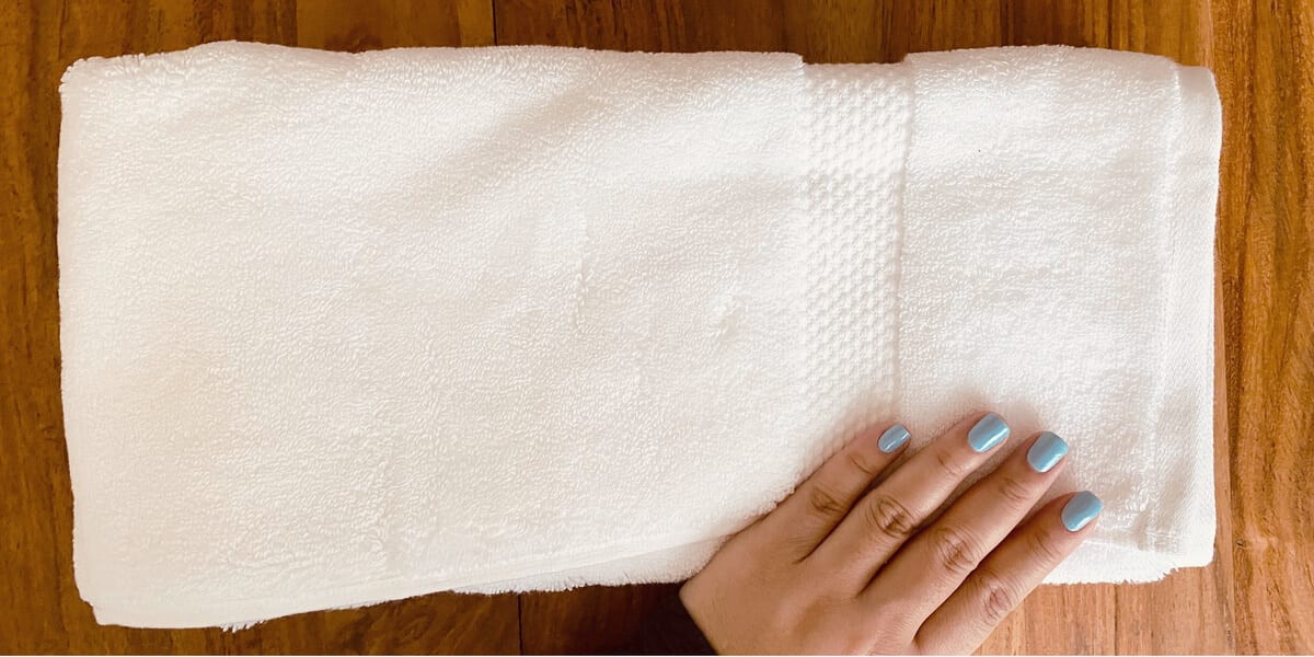 white towel folded into thirds on a wooden table