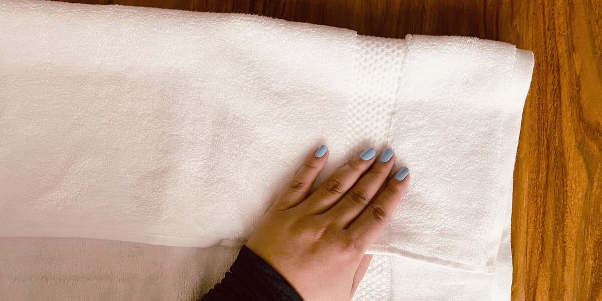 folding the corner of a white towel