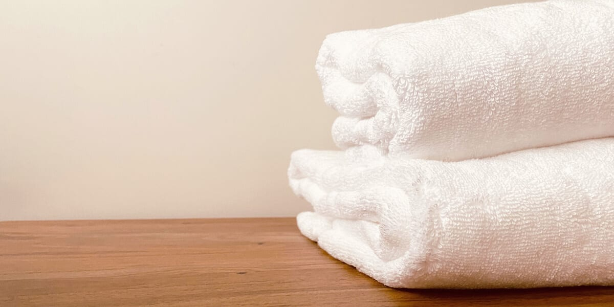 two white towels stacked on a wooden table