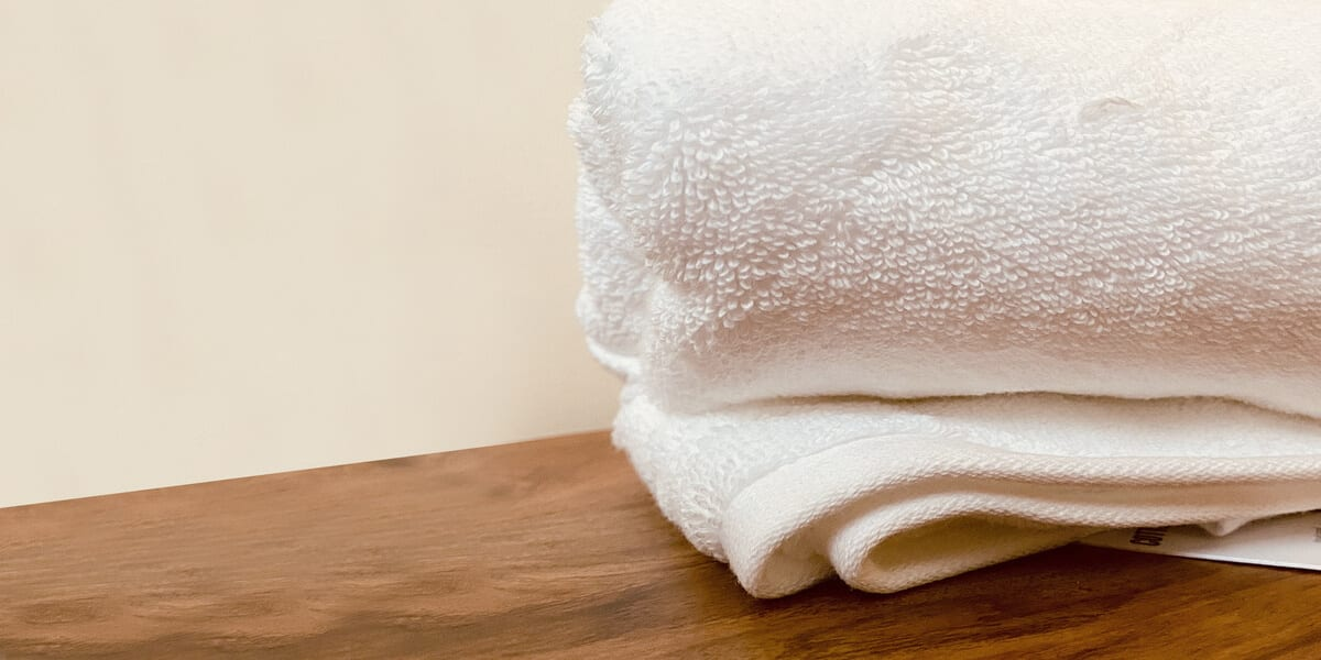 close up of white towels stacked on wooden table