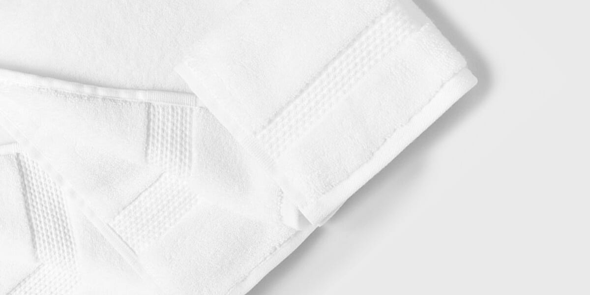 folded white towels stacked on top of one another