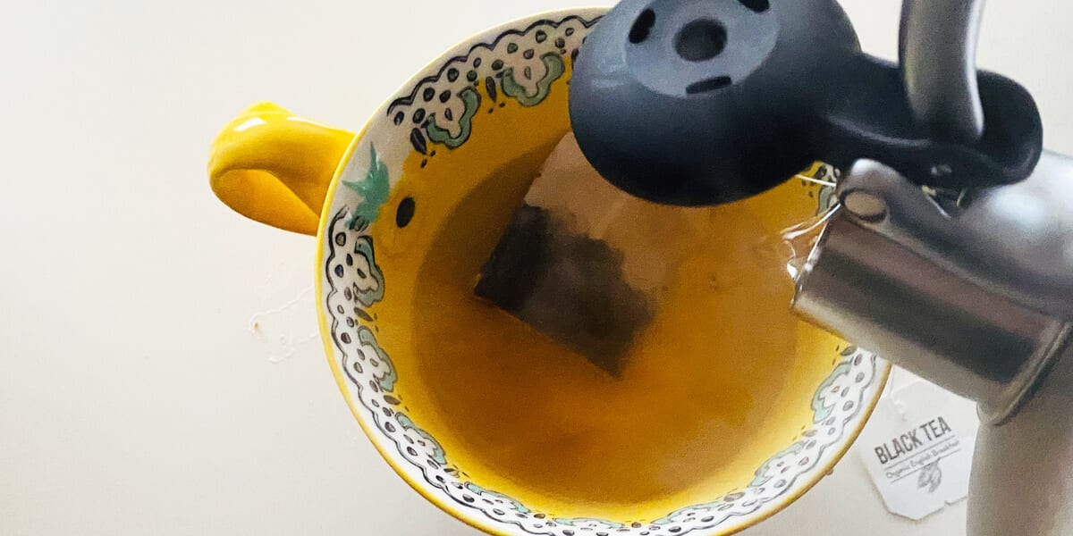 pouring hot water from tea kettle into tea cup