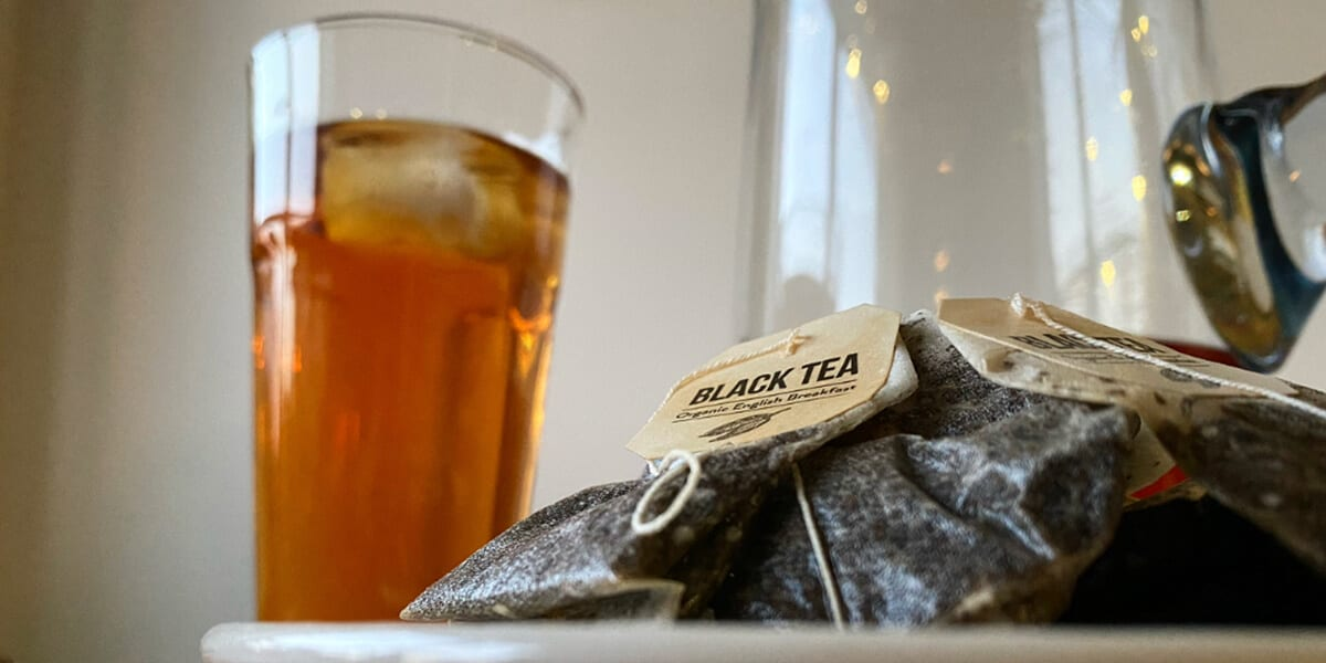 steeped black tea bags on table, glass of iced tea