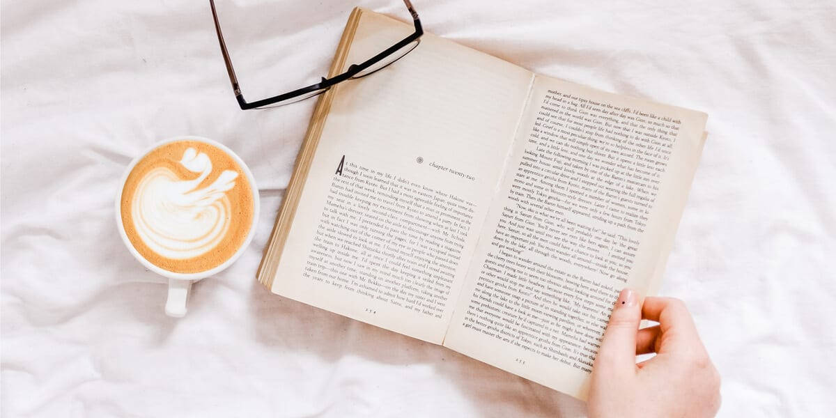 book, glasses, hand, coffee with heart in foam