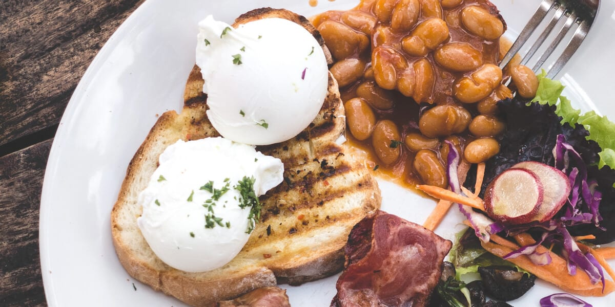plate with poached eggs, toast, beans, bacon, carrots, lettuce, radishes, fork.