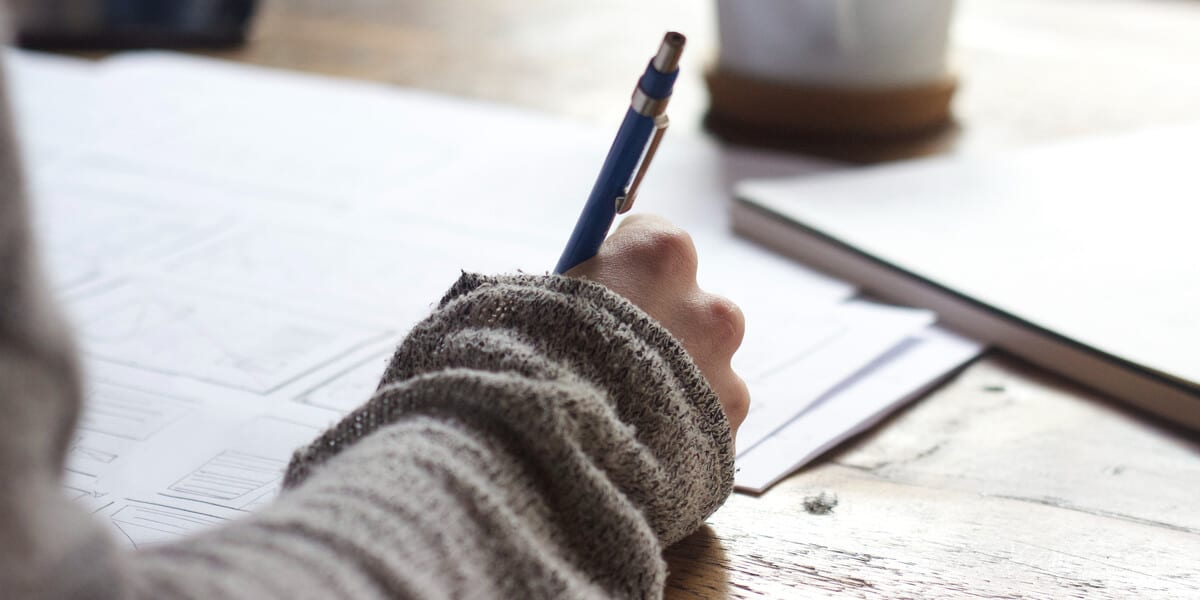 person filling out forms with a pen