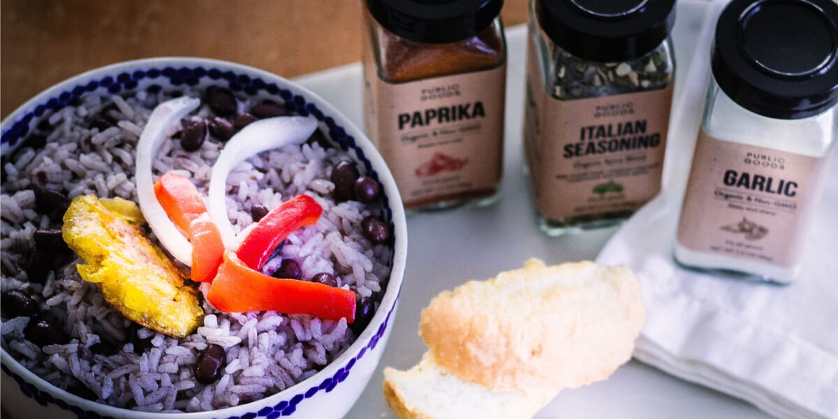jar of public goods italian seasoning, jar of public goods garlic powder, jar of public goods paprika, mixed white rice and black beans topped with sliced onion sliced and red pepper in a bowl, cuban bread, napkins