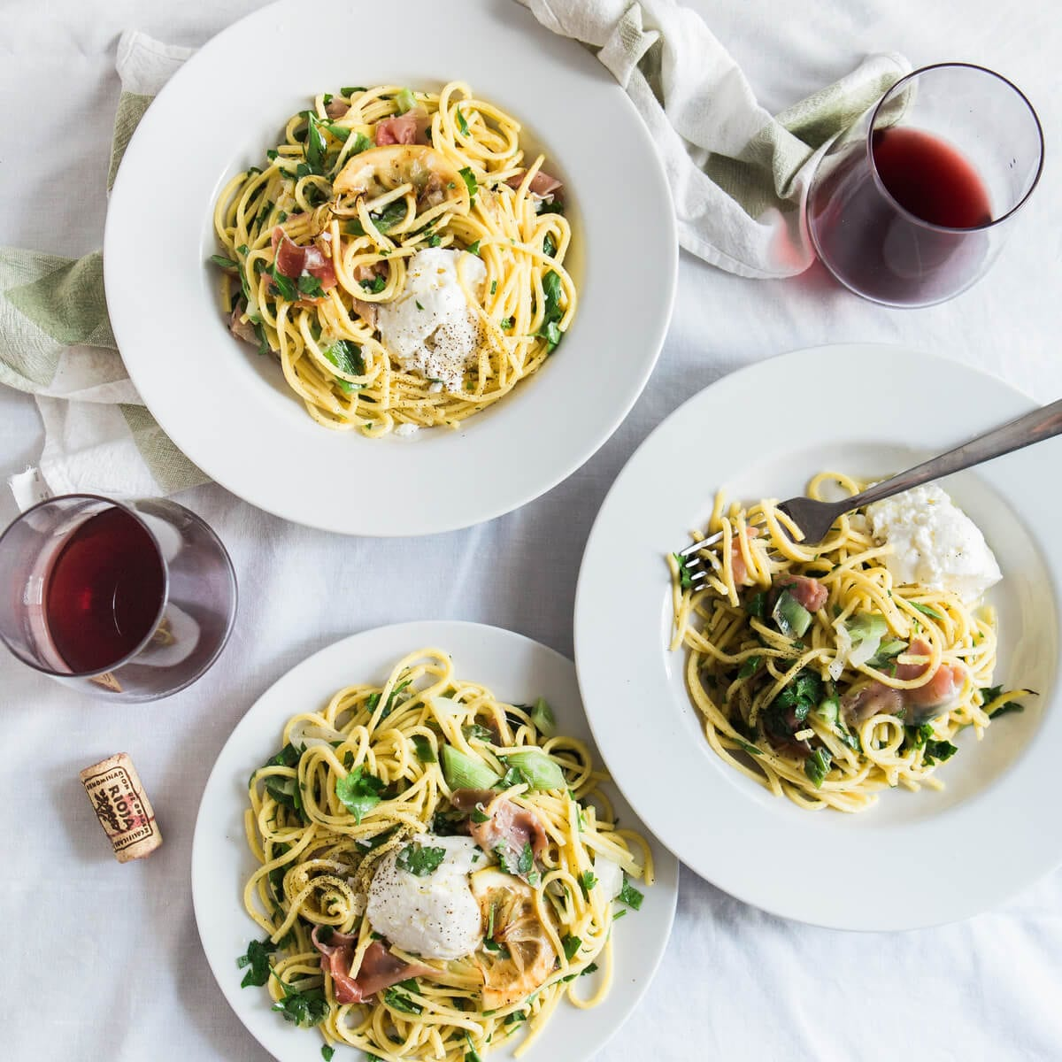three bowls of pasta,two wine glasses with red wine, cork