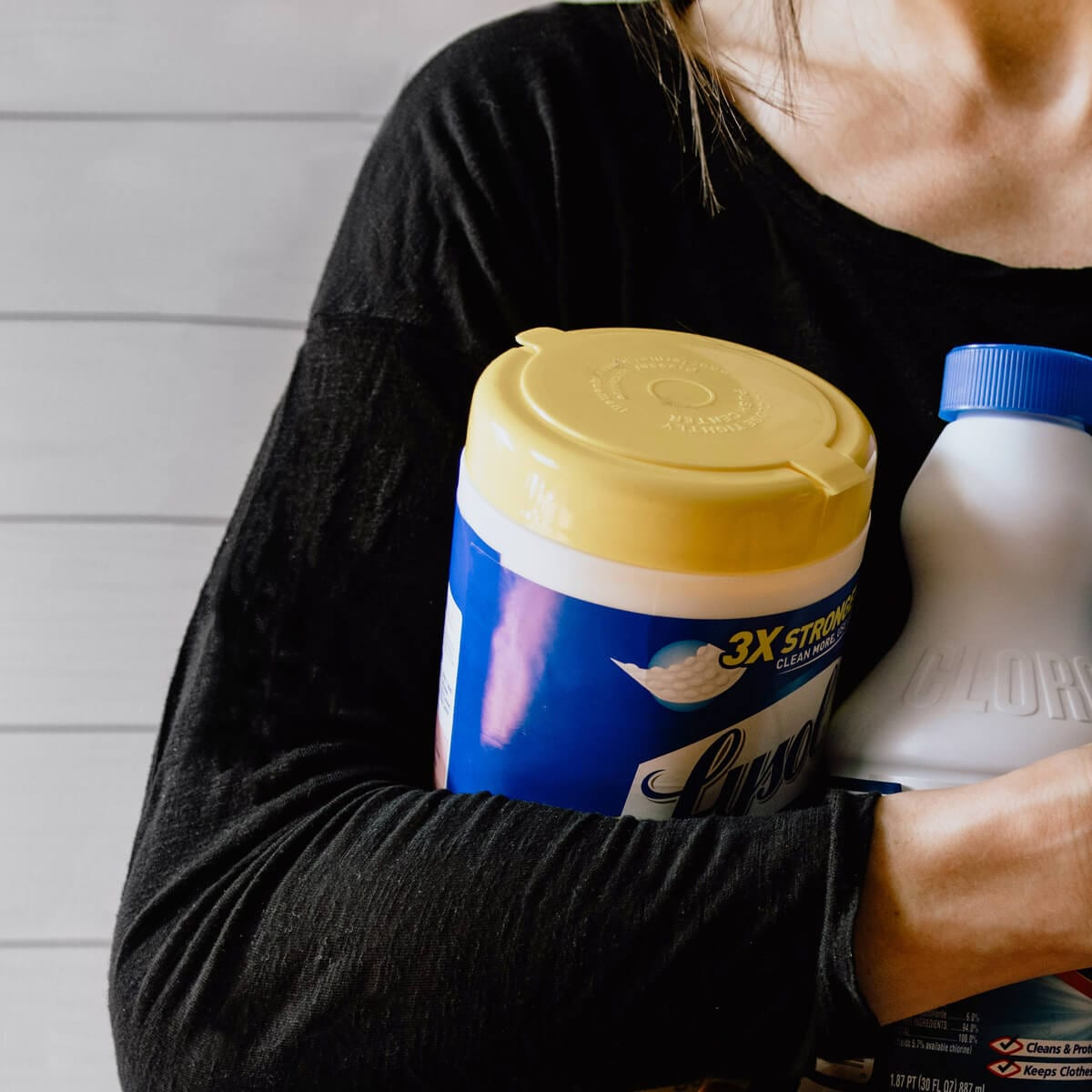 woman holding a bottle of bleach and a container of lysol disinfectant wipes
