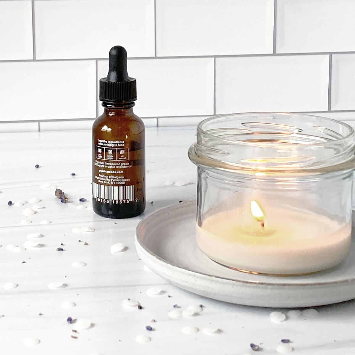 lit candle in a glass jar, bottle of essential oil